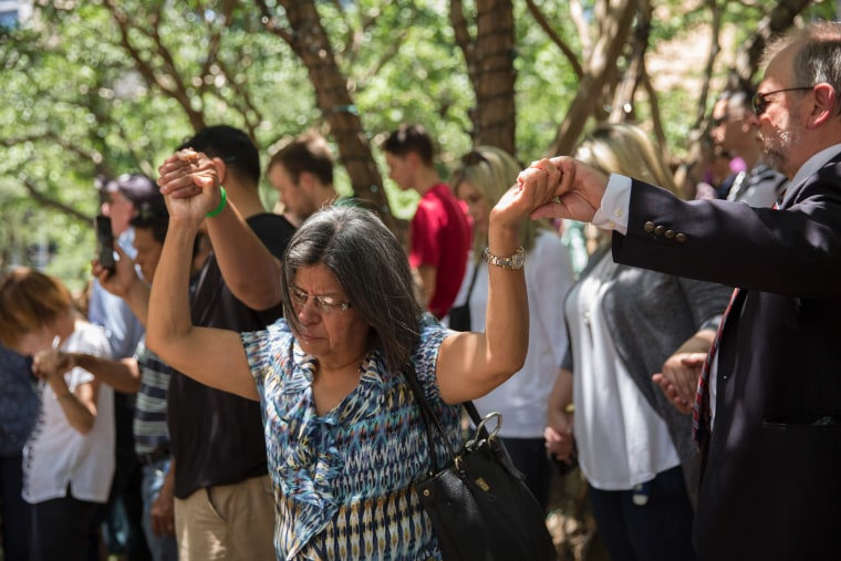 Image: People pray at a faith vigil at Thanks-Giving Square in Dallas