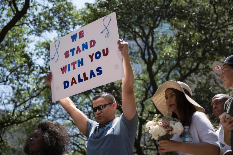 "Image: A man holds a sign reading ""We Stand With You Dallas"" during a vigil at Thanks-Giving Square in Dallas"