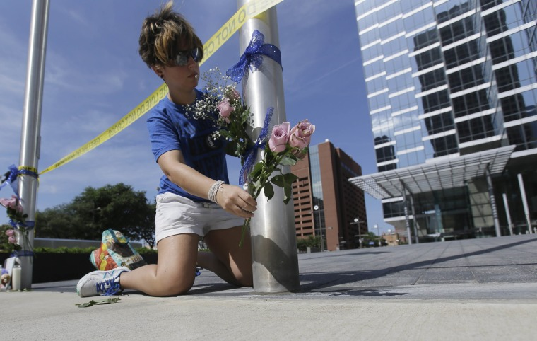Image: Noelle Hendrix places flowers near the scene of a shooting in downtown Dallas