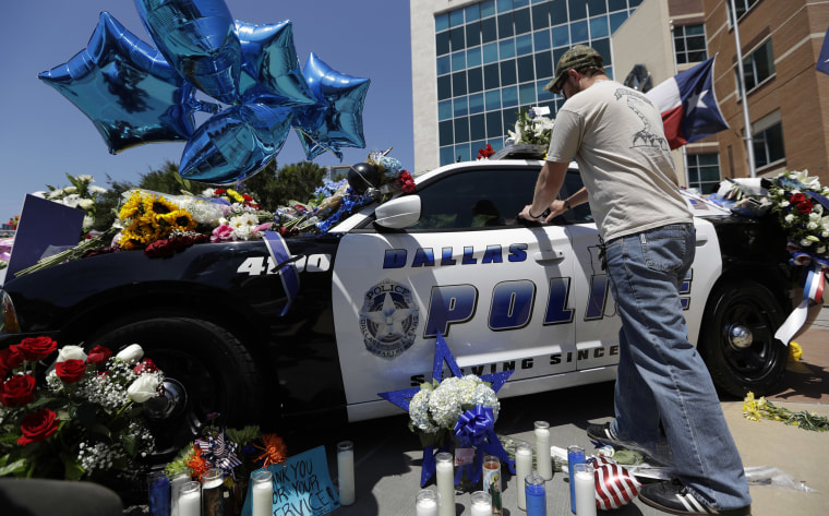 Image: Michael O'Mahoney, a former police officer, places his patch on a make-shift memorial at the Dallas police headquarters