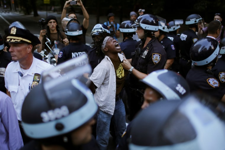 Image: A protestor is detained by NYPD officer as people take part in a protest for the killing of Alton Sterling and Philando Castile during a march along Manhattan's streets in New York