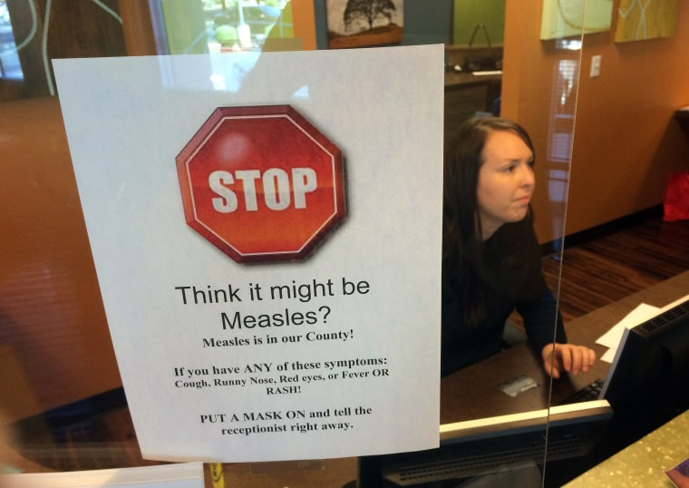 Image: A sign warns of the dangers of measles in the reception area of a pediatrician's office