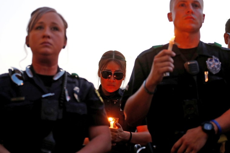 Image: Dallas police officers take part in a candlelight vigil at Dallas City Hall following the multiple police shootings in Dallas
