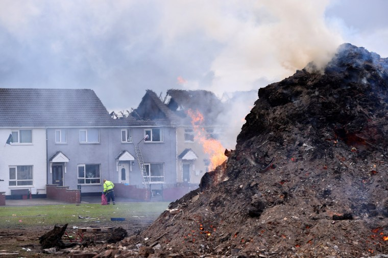 Image: Three houses are seen burnt down from a bonfire in the Shankill Road area as a result of the Eleventh night celebrations held by Loyalists in Belfast