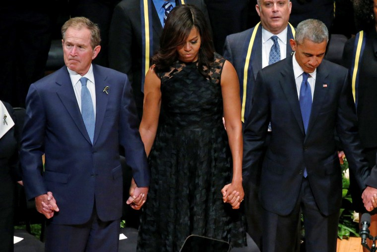 Image: Former president George W. Bush (L) First Lady Michelle Obama (C) and U.S. President Barack Obama sing during a memorial service following the multiple police shootings in Dallas