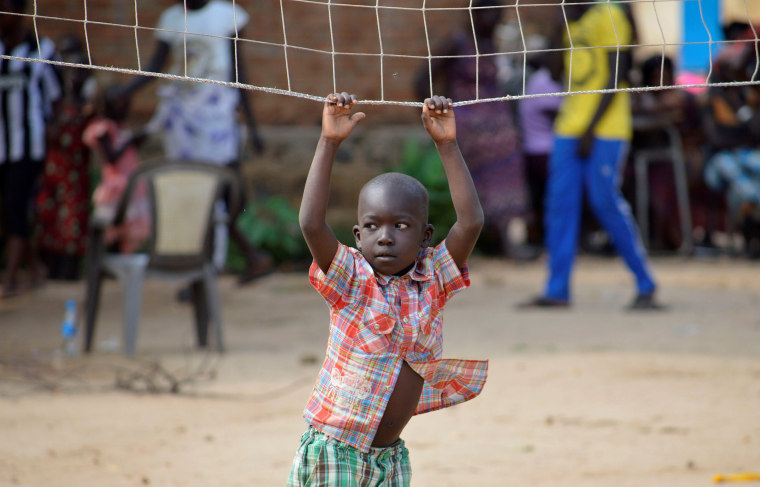 Image: A boy displaced in recent fighting plays on a volleyball net as they camp at the Anglican church compound in Juba, South Sudan