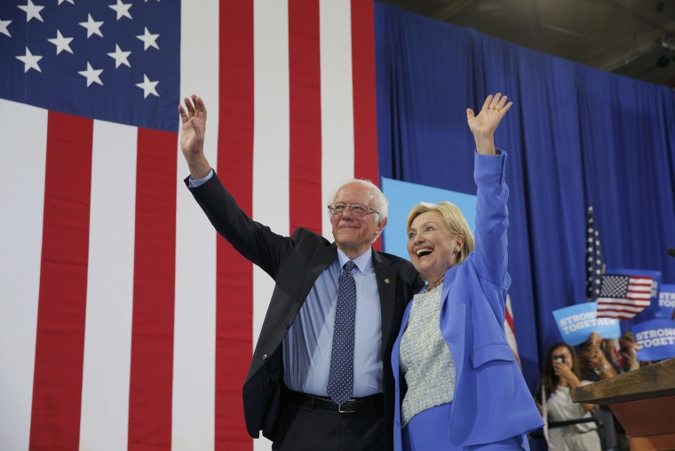 Image: Democratic U.S. presidential candidates Clinton and Sanders stand together during campaign rally in Portsmouth, New Hampshire