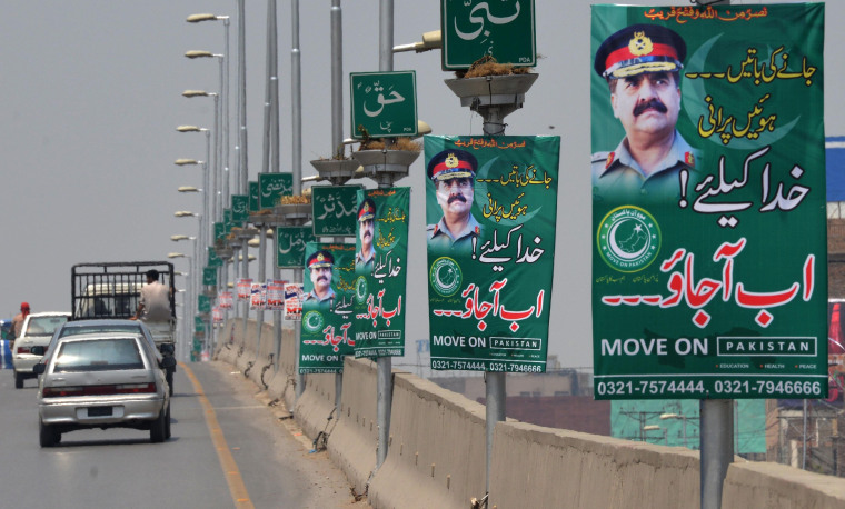 Image: Commuters in Peshawar drive past posters begging Pakistan's powerful army chief Gen. Raheel Sharif to launch a coup
