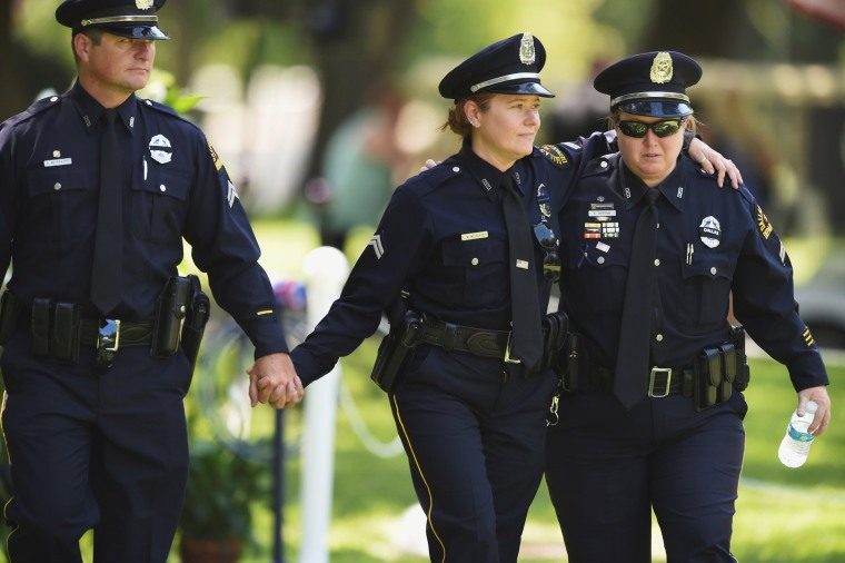 Image: Officers leave the burial ceremony of Dallas Police Department Senior Corporal Lorne B. Ahrens, who was among five police officers shot dead the previous week, at Restland Public Safety Memorial Gardens in Dallas