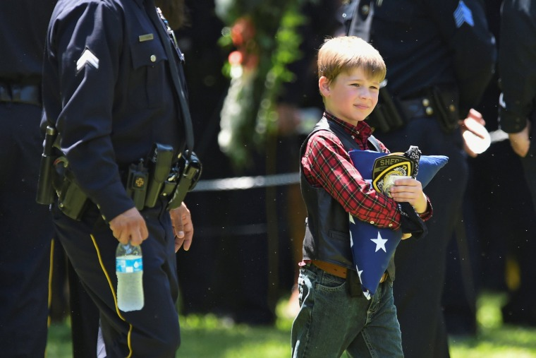 Image: Magnus Ahrens carries a folded U.S. flag after the burial ceremony for his father, Dallas Police Department Senior Corporal Lorne B. Ahrens, who was among five police officers shot dead the previous week, at Restland Public Safety Memorial Gardens