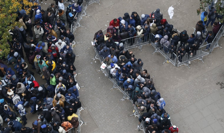 Image: Migrants queue outside Office of Health and Social Affairs as they wait to register in Berlin