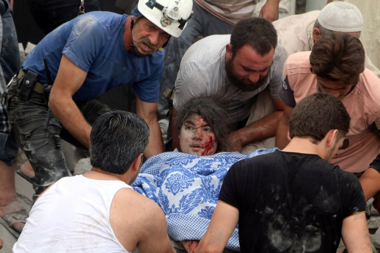 Image: Men carry an injured girl after an airstrike on Aleppo's rebel held Kadi Askar area