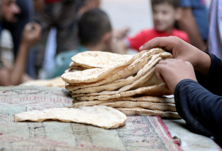 Image: A boy arranges bread in the rebel held al-Shaar neighbourhood of Aleppo