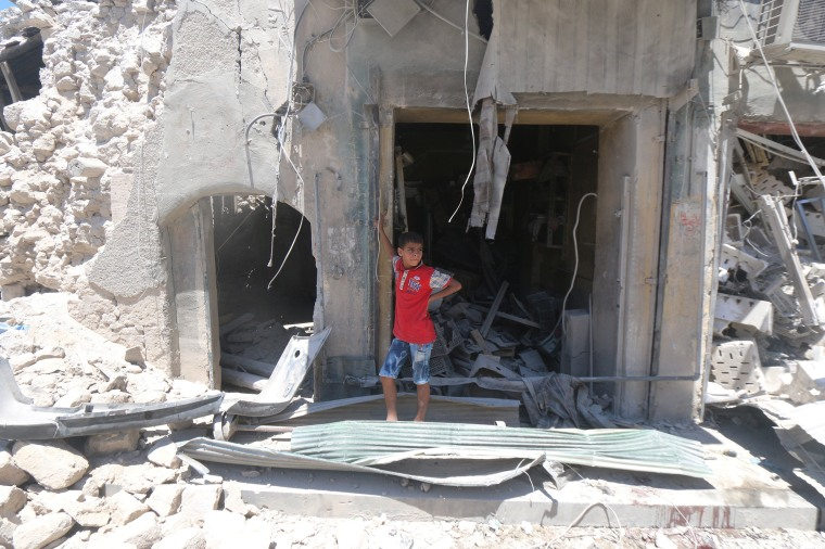 Image: A boy stands at a site hit by a barrel bomb in the rebel held area of Old Aleppo