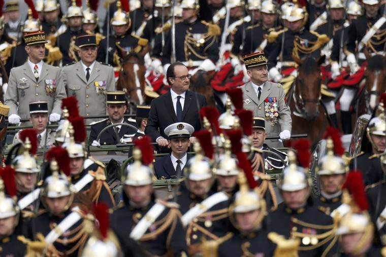 Image: French President Francois Hollande stands at attention in the command car as he reviews the troops while descending the Champs Elysees at the start of the traditional Bastille Day military parade in Paris