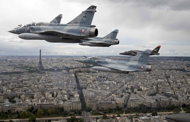 Image: Four Mirage 2000C and one Alpha jet flight over Paris on their way to participate in the Bastille Day military parade