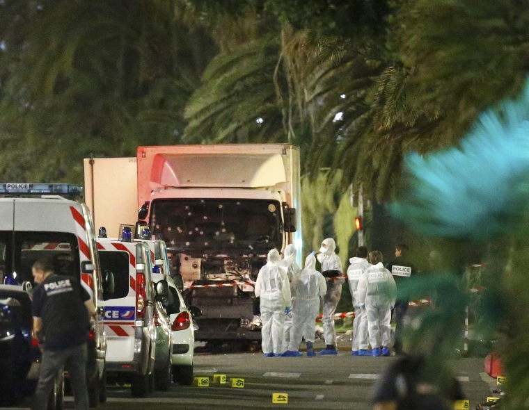 Image: French police forces and forensic officers stand next to a truck that ran into a crowd celebrating the Bastille Day national holiday on the Promenade des Anglais killing at least 60 people in Nice