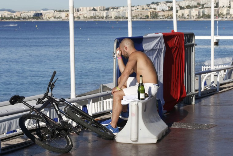 Image: A man reacts as he sits near a French flag along the beachfront the day after a truck ran into a crowd at high speed killing scores celebrating the Bastille Day July 14 national holiday on the Promenade des Anglais in Nice