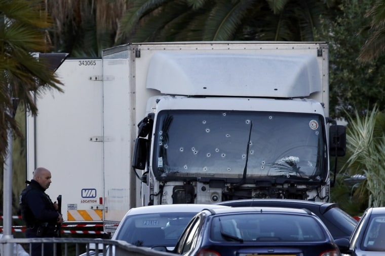 Image: French CRS police secure the heavy truck that ran into a crowd at high speed killing scores celebrating the Bastille Day July 14 national holiday on the Promenade des Anglais killing 80 people in Nice