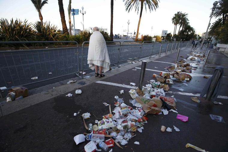 Image: A man walks through debris on the street the day after a truck ran into a crowd at high speed killing scores celebrating the Bastille Day July 14 national holiday on the Promenade des Anglais in Nice