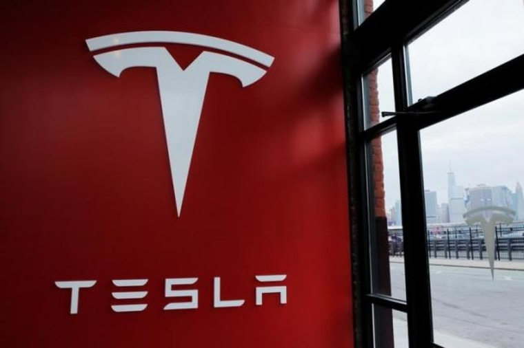 A Tesla logo is painted on a wall inside of a Tesla dealership in New York