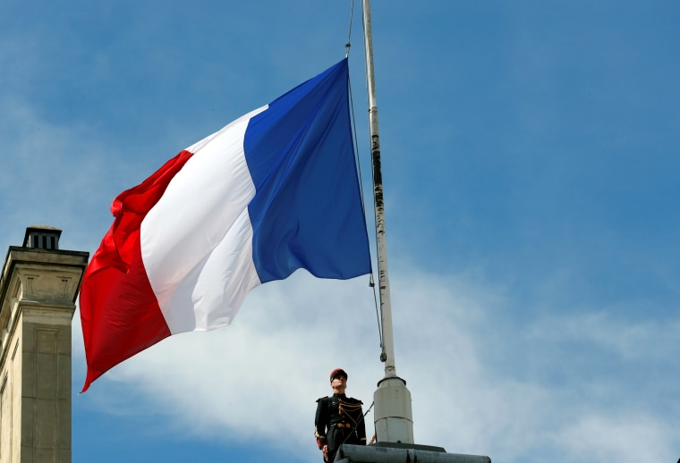Image: A Republican Guard pays his respects after lowering the French national flag at half-mast at the Elysee Palace in Paris