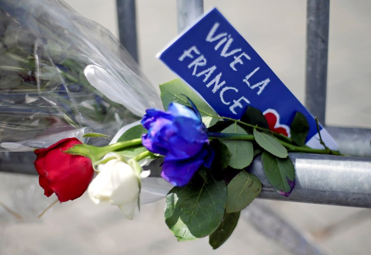 Image: Flowers are seen attached to a fence to remember the victims of the Bastille Day truck attack in Nice in front of the French embassy in Rome