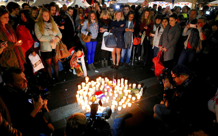 Image: Members of the Australian French community stand around candles during a vigil in central Sydney