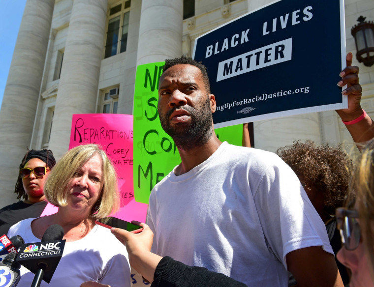 Lawyer Patricia Kane of New Haven, second from left, with her client Corey Menafee, a former employee at Yale's Calhoun College who was arraigned for breaking a window pane depicting black slaves picking cotton at Calhoun College, right, talk with the press as they leave New Haven Superior Court on Chapel Street in New Haven on July 12, 2016.