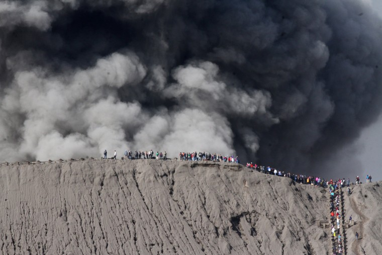 Image: People standing on the edge of the crater while watching the eruption of Mount Bromo in Probolinggo