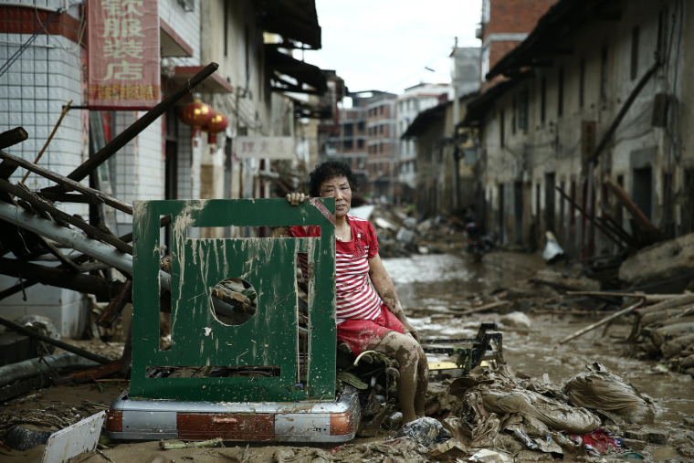 Image: A woman sits on ruins after typhoon Nepartak swept through Minqing county