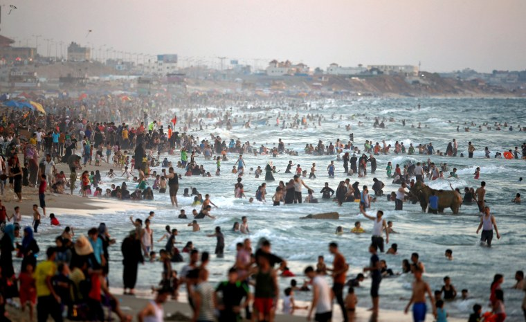 Image: Palestinians cool off in the Mediterranean sea during a hot day in Gaza City