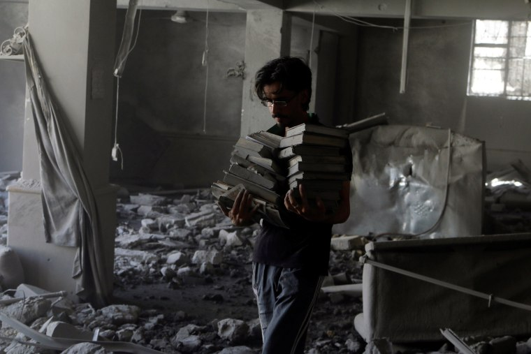 Image: A man carries Koran books he collected amid damage inside al-Aqsa mosque after an airstrike in Aleppo, Syria