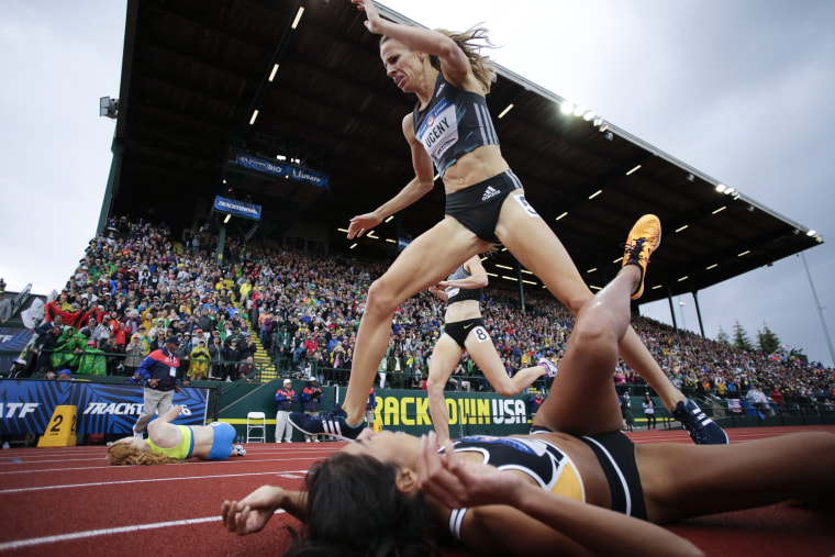 Image: Morgan Uceny, top, steps over Brenda Martinez at the finish line in the finals of the women's 1500-meter run