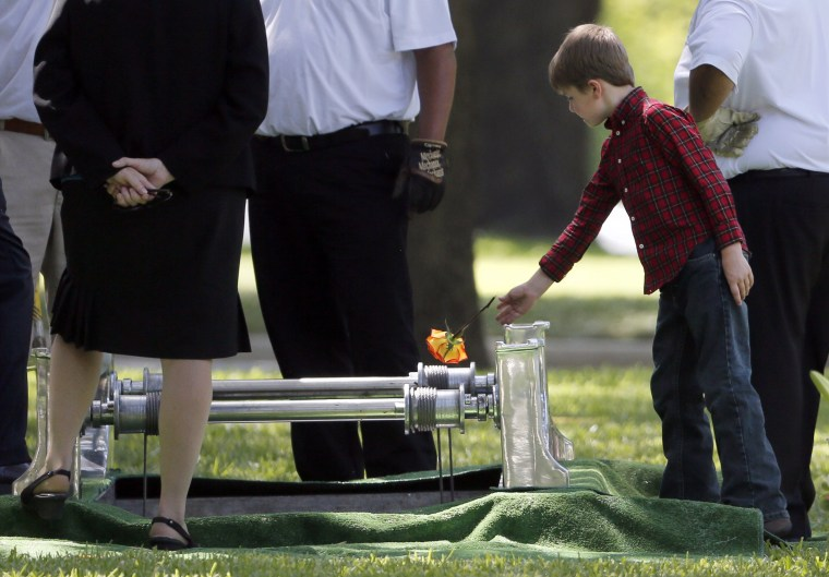 Image: Magnus Ahrens, 8, tosses a flower into the grave of his father