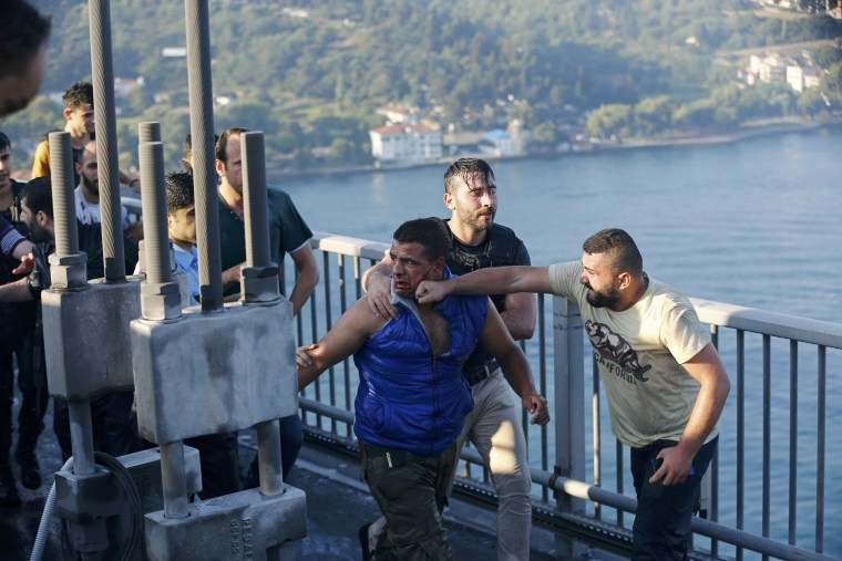 Image: A civilian beats a soldier after troops involved in the coup surrendered on the Bosphorus Bridge in Istanbul