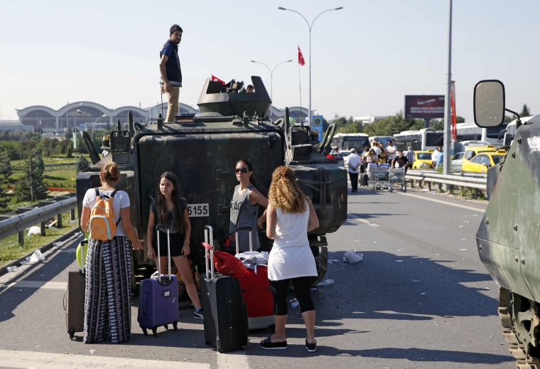Image: Women stand behind a military vehicle in front of Sabiha Airport, in Istanbul