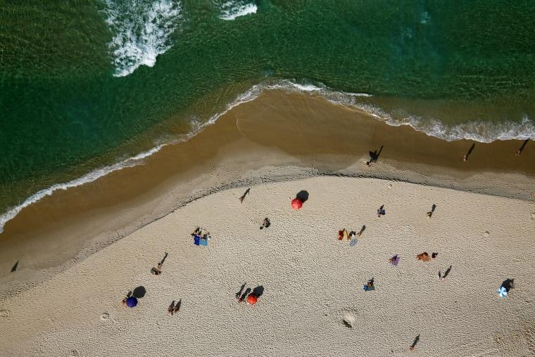 Image: People enjoy the sun at Barra da Tijuca beach in Rio de Janeiro