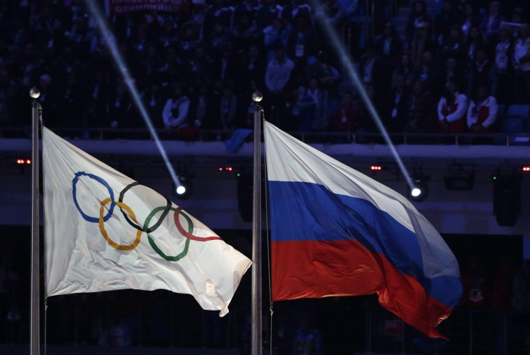 FILE- In this Feb. 23, 2014, file photo, the Russian national flag, right, flies after next to the Olympic flag during the closing ceremony of the 2014 Winter Olympics in Sochi, Russia.