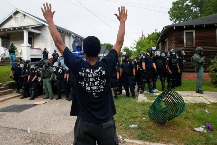 Image: A demonstrator raises his hands in front of police in riot gear during protests in Baton Rouge
