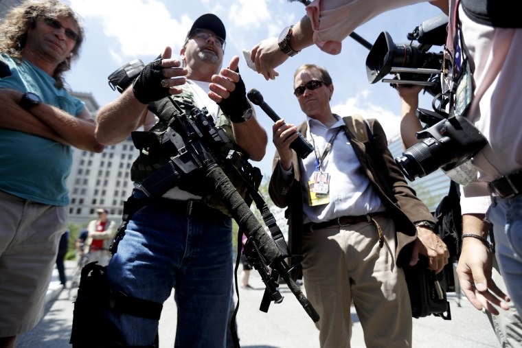 Image: Second Amendment supporter Steve Thacker carries an AR-15-style weapon as he talks to the media during a protest