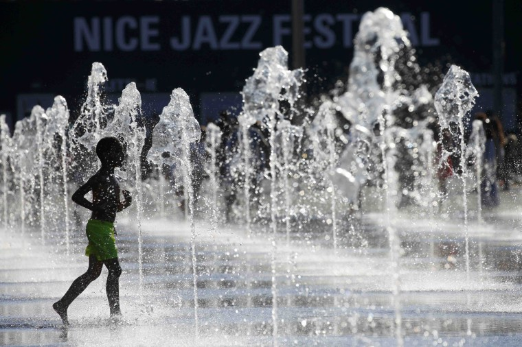Image: A child cools off in fountains as summer weather continues in Nice