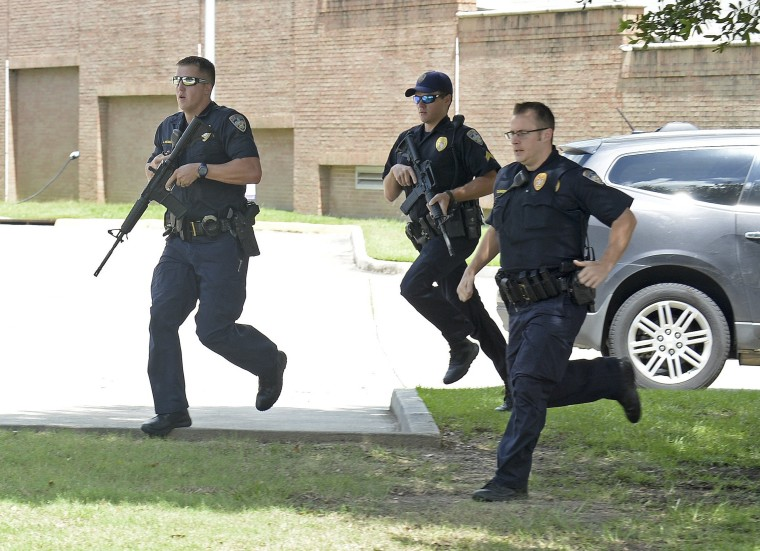Image: Baton Rouge Police run from the emergency room ramp as a man is taken into custody after a gun was found in his vehicle