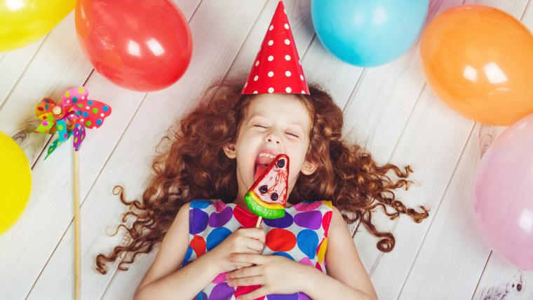 little girl licking a lollipop.
