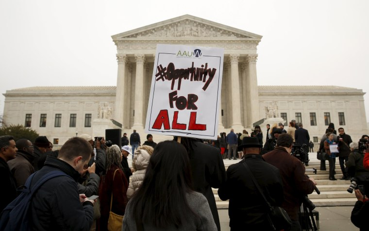 Image: A demonstrator holds a sign aloft as the affirmative action in university admissions case was being heard at the Supreme Court in Washington