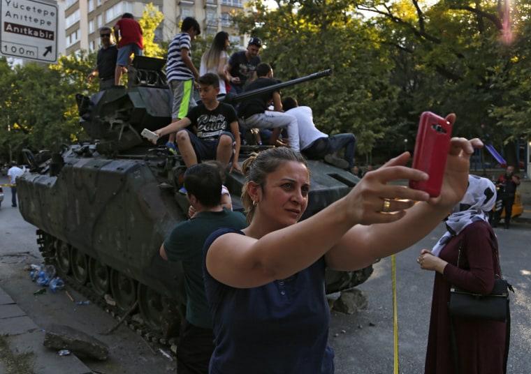 Image: Woman takes a self near Turkish military vehicle on July 16, 2016