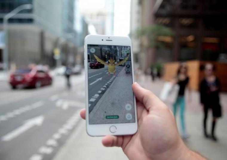 "Photo illustration of a \""Pidgey\"" Pokemon seen on the screen of the Pokemon Go mobile app"