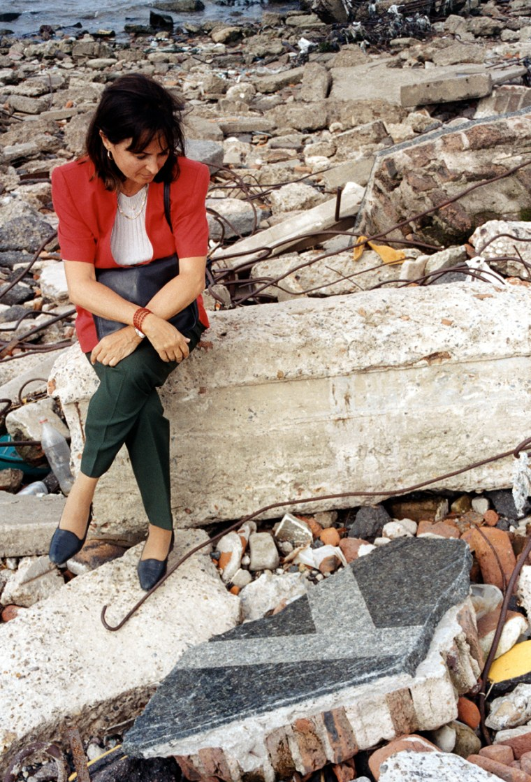 Women sits in the wreckage left behind after the Argentinian Jewish Center Bombing that killed over 80 people.