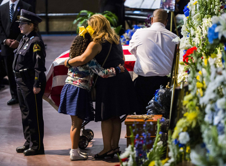Image: Family members share a moment during a funeral service during a funeral service for police officer Zamarripa, a former U.S. Navy veteran, who was among five police officers shot dead the previous week, in Fort Worth