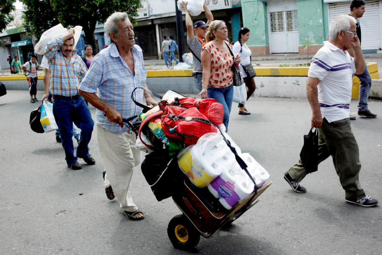 Image: A man push a trolley with toilet paper and other goods as he walks towards  the Colombian-Venezuelan border after shopping in Cucuta, Colombia